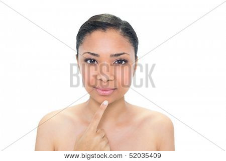 Stern young dark haired model touching her chin on white background