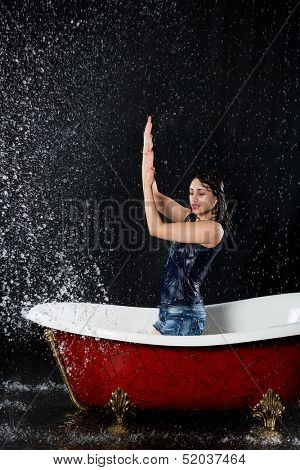 Drenched girl protected from the water stands in the bathtub under the spray
