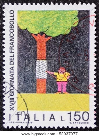 ITALY - CIRCA 1976: a stamp printed in Italy promotes environmental protection depicting a boy auscultating by stethoscope a wounded tree. Italy, circa 1976