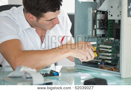 Handsome computer engineer repairing computer with pliers in bright office