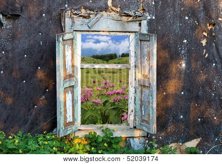 view on mountain's meadow though old window frame in abandoned house