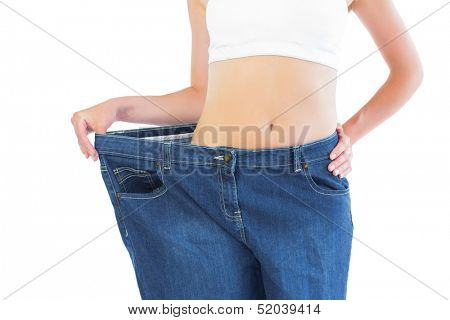 Close up of confident slender blonde wearing too big trousers on white background