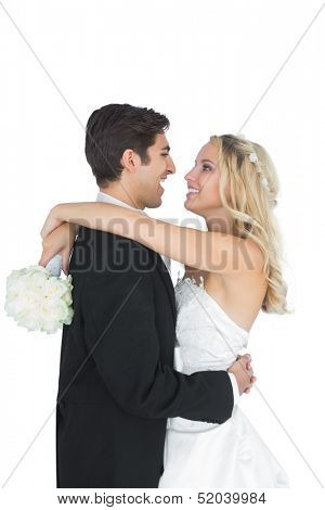 Happy young bridegroom hugging his wife on white background