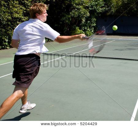 Tennis Player Smashing A Ball Across Court