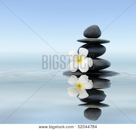 Zen spa concept background - Zen massage stones with frangipani plumeria flower in water reflection