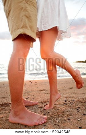Love - romantic couple dating on beach kissing and embracing. Happiness and romance travel concept with happy young couple barefoot in sand enjoying beautiful sunset.