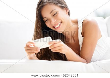 Smartphone woman using app on mobile smart phone smiling happy. Beautiful multiracial girl sms text messaging or using application while lying on sofa. Asian Caucasian model in her 20s.