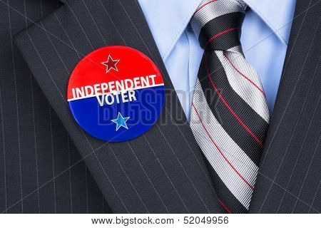An independent voter wears his party pin on his suit lapel