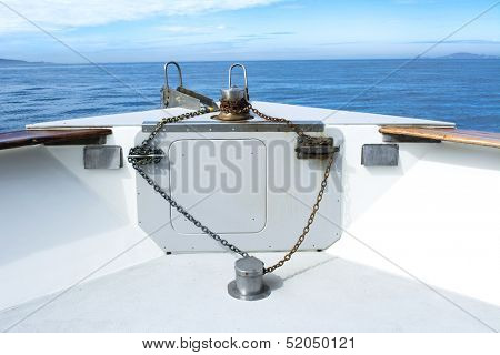 The bow of a passenger cruise boat shows its rusty anchor chain, cleats and winch amongst a blue sky and distant islands.