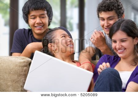 Teenagers Discussing Something Interesting On Laptop