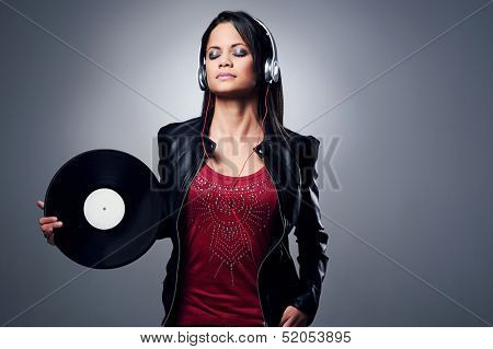 Woman dj portrait with vinyl record and headphones
