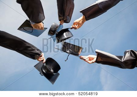 Directly below shot of students raising mortar boards against sky on graduation day