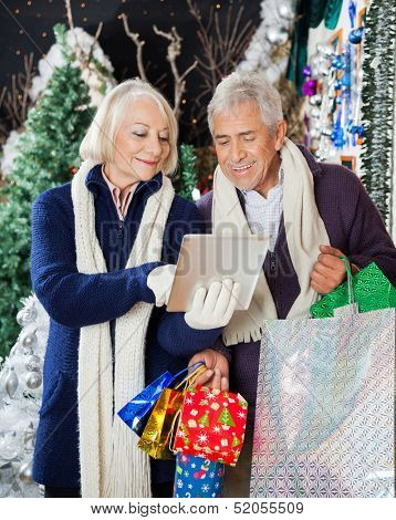 Senior couple with shopping bags using digital tablet together at Christmas store
