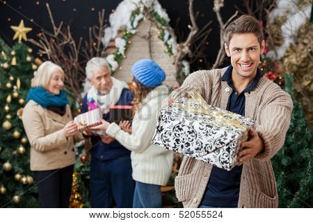 Portrait of happy man offering Christmas present with family standing in background at store