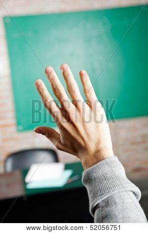 Cropped image of student's hand against greenboard in classroom