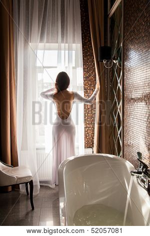 Attractive Woman Looking At Window And Preparing To Take A Bath