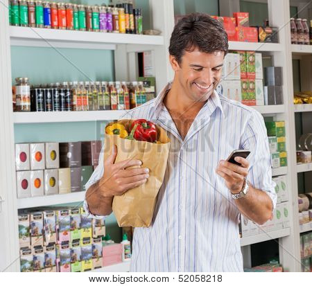 Happy male customer with grocery paper bag using mobile phone in supermarket