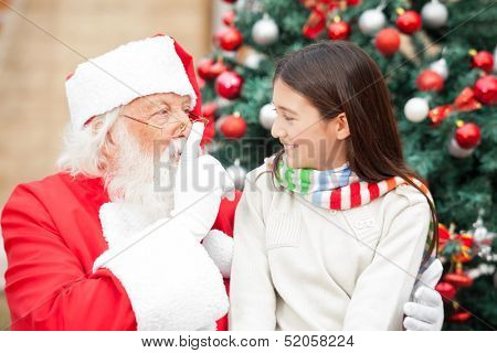 Santa Claus gesturing finger on lips at girl in front of Christmas tree
