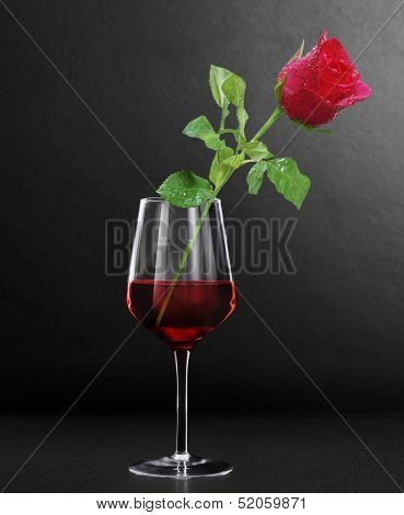 Glass of red wine and a roses