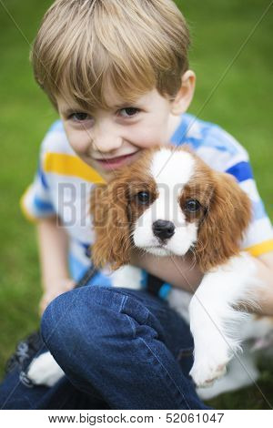 Boy With Pet King Charles Spaniel Puppy