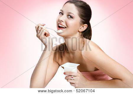 Charming woman eating yogurt