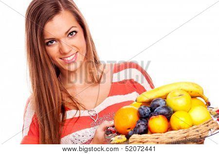 Beautiful brunette holding a punnet full of fresh fruit