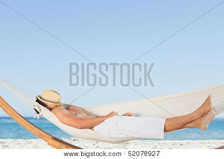 Man wearing straw hat relaxing in a hammock on the beach on holidays