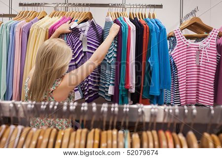 Woman is searching clothes in a boutique