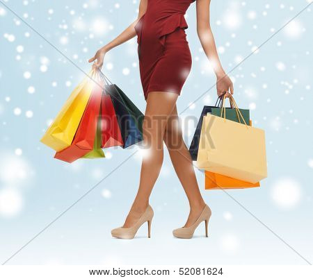 shopping, sale, gifts, christmas, x-mas concept - woman's long legs with shopping bags