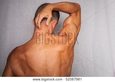 Back Of Young Muscular Man Above Gray Background