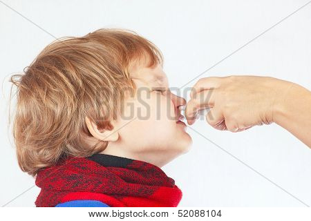 Little sick boy used medical nasal spray in the nose