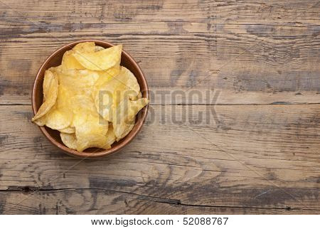 Cheese and chive potato crisp snack in brown bowl on wooden background