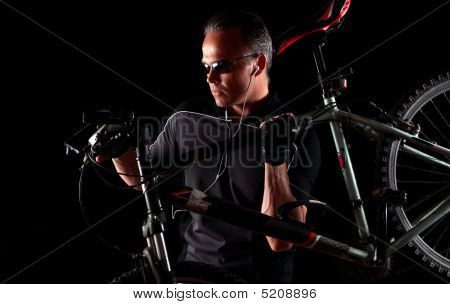Male Cyclist Carrying Mountain Bike