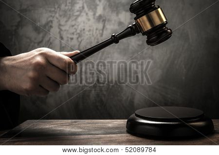 Judge's hand holding wooden hammer