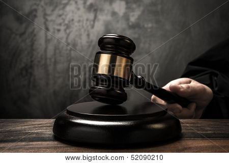 Judge's hand holding wooden hammer