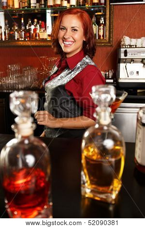 Beautiful redhead barmaid behind bar counter