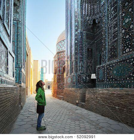 Young lady tourist enjoying oriental atmosphere of ancient complex of Shah i Zinda. Samarkand, Uzbekistan