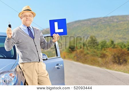 Senior man posing on his car, holding a L sign and car key after having his driver's licence on an open road