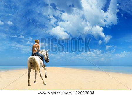 Young female riding her horse in the sea on tropical beach