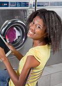picture of laundromat  - Portrait of young African American woman holding digital tablet sitting at laundromat - JPG