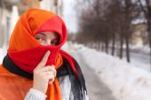 stock photo of yashmac  - young beautiful woman in red purdah against street - JPG