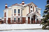 stock photo of peace-pipe  - Big cottage with red roof and white drain at frosty and sunny winter day - JPG
