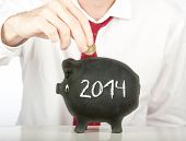 businessman putting money on a piggy bank with a year 2014 drawing