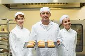 Young male baker holding a baking tray with rolls on it posing with colleagues