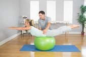 pic of physiotherapist  - Physiotherapist helping patient doing exercise with exercise ball in bright room - JPG