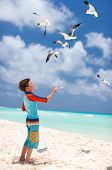 foto of flock seagulls  - Little boy and a flock of seagulls at beach - JPG