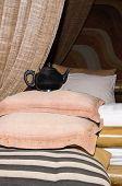 stock photo of futon  - Old tea pot on a pile of pillows - JPG