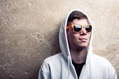 foto of hooded sweatshirt  - Street portrait of young boy in white sweatshirt with orange modern eyeglasses and hood near old wall street atmosphere landscape young generation street life - JPG