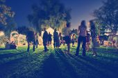 image of moonlit  - people mingling at a free concert by local musicians - JPG