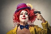 foto of tragic  - beautiful clown is pointing a gun to her head - JPG